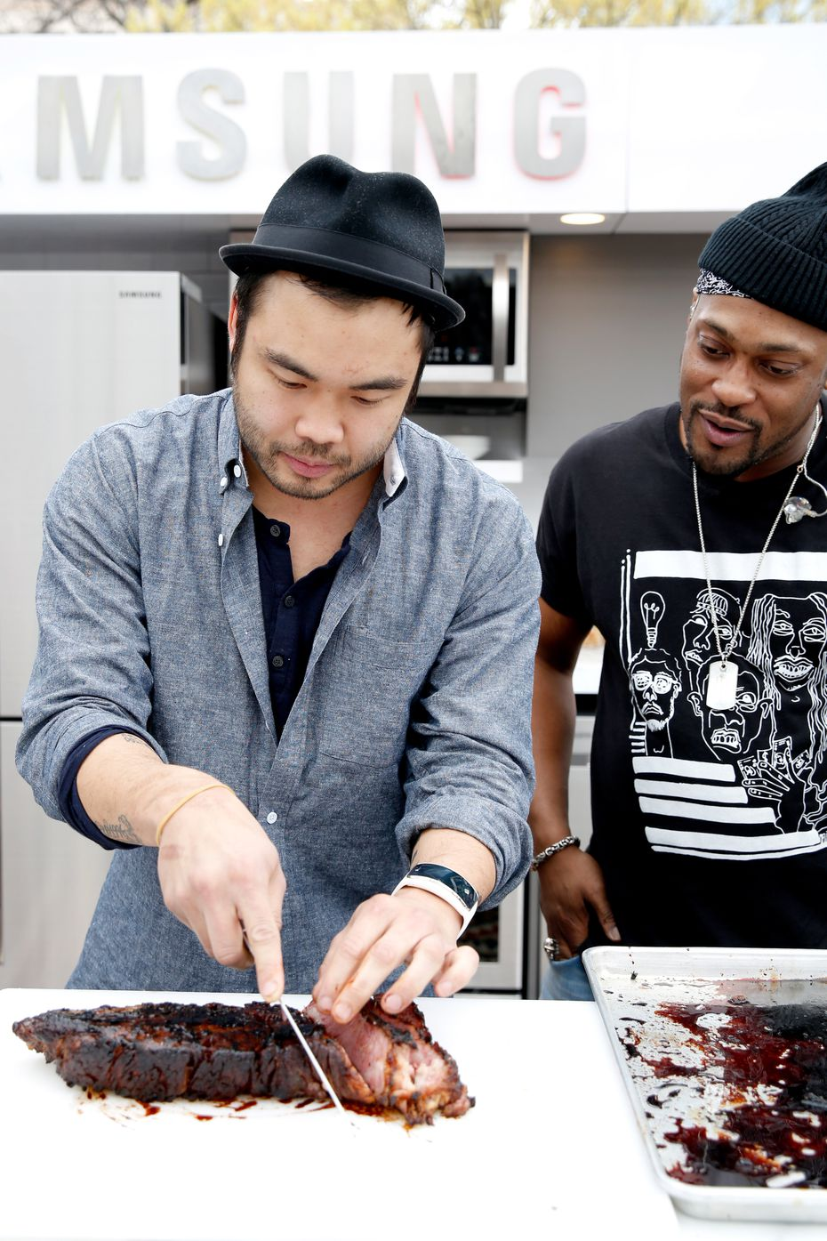 Chef Paul Qui (left) slices meat while singer/songwriter D'Angelo looks on at SXSW 2015 in Austin, Texas