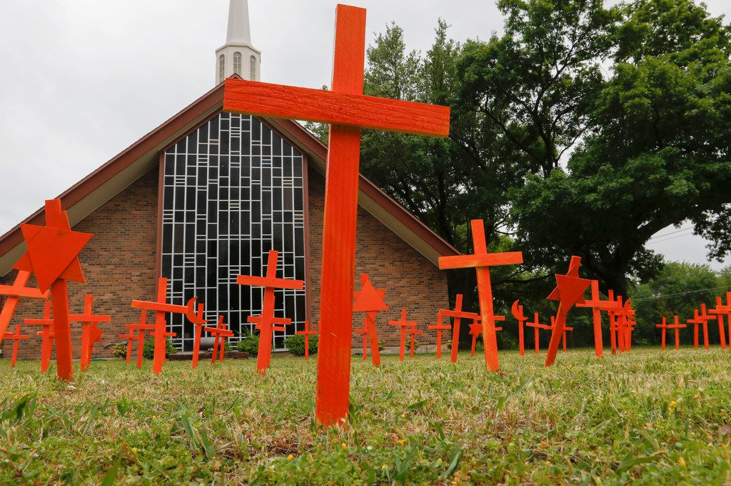 Ninety-six orange crosses, Stars of David and crescent moons-and-stars meant to represent the number of people killed every day by gun violence are displayed in front of Central Congregational Church on Royal Lane near the Dallas North Tollway.