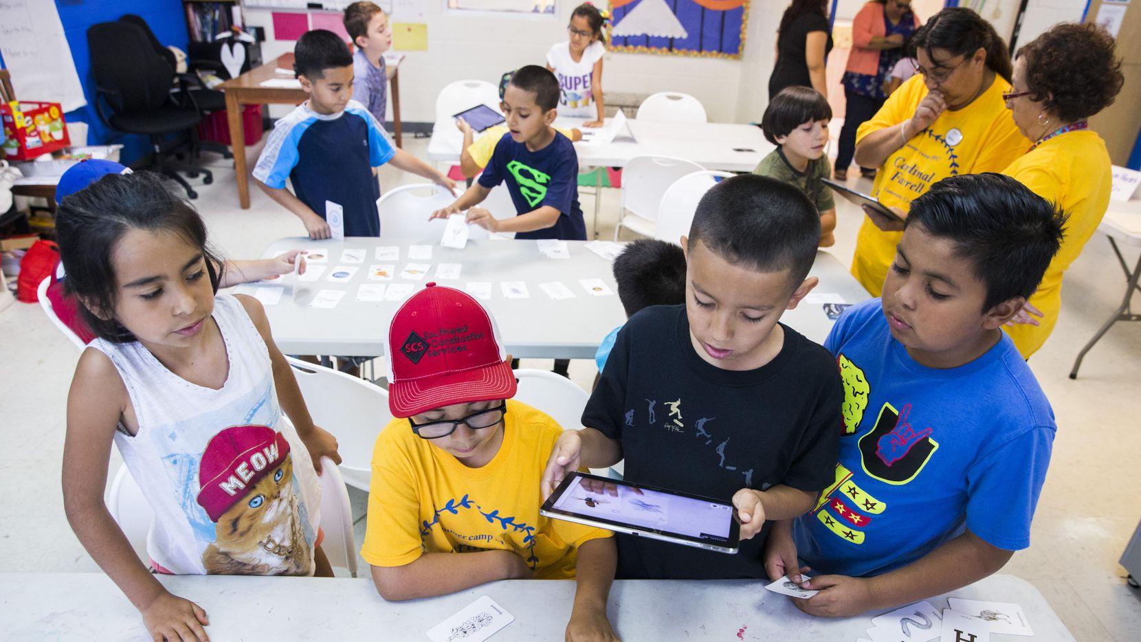 Alumnos de tercer grado aprenden en una tableta de 4D durante el programa de aprendizaje de Catholic Charities. (DMN/ASHLEY LANDIS)