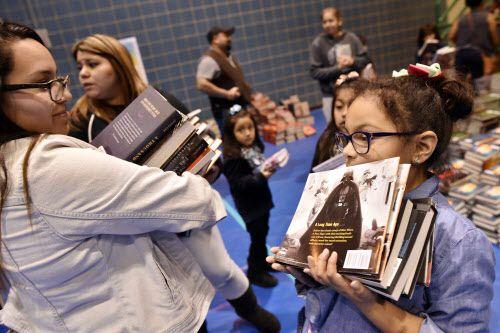 Celina Morantes (izq.) y su hija Alazy, de 7 años, se llevan varios libros durante un festival de donación de libros en el sur de Dallas.