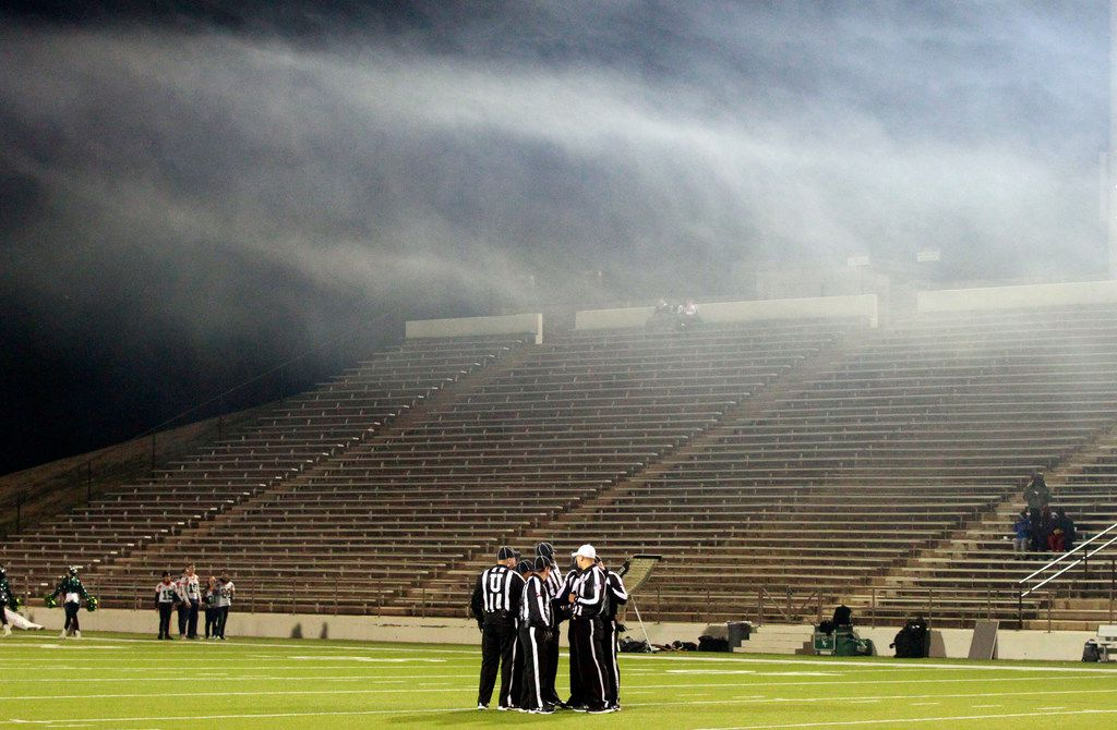 Games officials confer under a cloud of smoke before the start of the Naaman Forest Vs. Lakeview Centennial high school football game at Homer B. Johnson Stadium on Friday, November 8, 2019. (John F. Rhodes / Special Contributor)