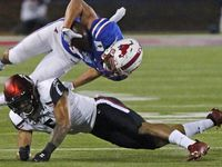 Southern Methodist Mustangs wide receiver Tyler Page (4) is upended by Cincinnati Bearcats safety Darrick Forrest (5) during the second half as SMU hosted Cincinnati University in an AAC football game at Ford Stadium in Dallas on Saturday night, October 24, 2020.