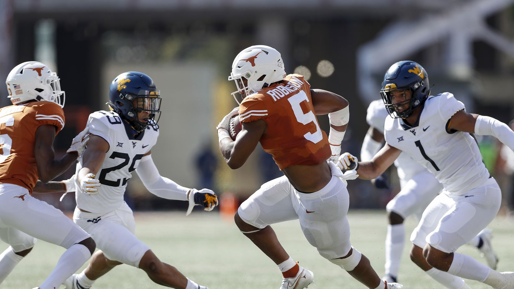 Texas running back Bijan Robinson (5) runs the ball while defended by West Virginia linebacker Tony Fields II (1) and safety Sean Mahone (29) in the first quarter at Darrell K Royal-Texas Memorial Stadium on Nov. 7, 2020 in Austin. (Photo by Tim Warner/Getty Images)