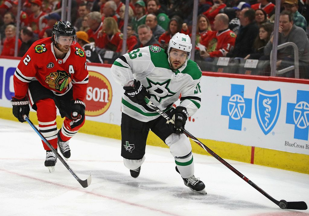 CHICAGO, ILLINOIS - FEBRUARY 24: Mats Zuccarello #36 of the Dallas Stars passes under pressure from Duncan Keith #2 of the Chicago Blackhawks at the United Center on February 24, 2019 in Chicago, Illinois. (Photo by Jonathan Daniel/Getty Images)