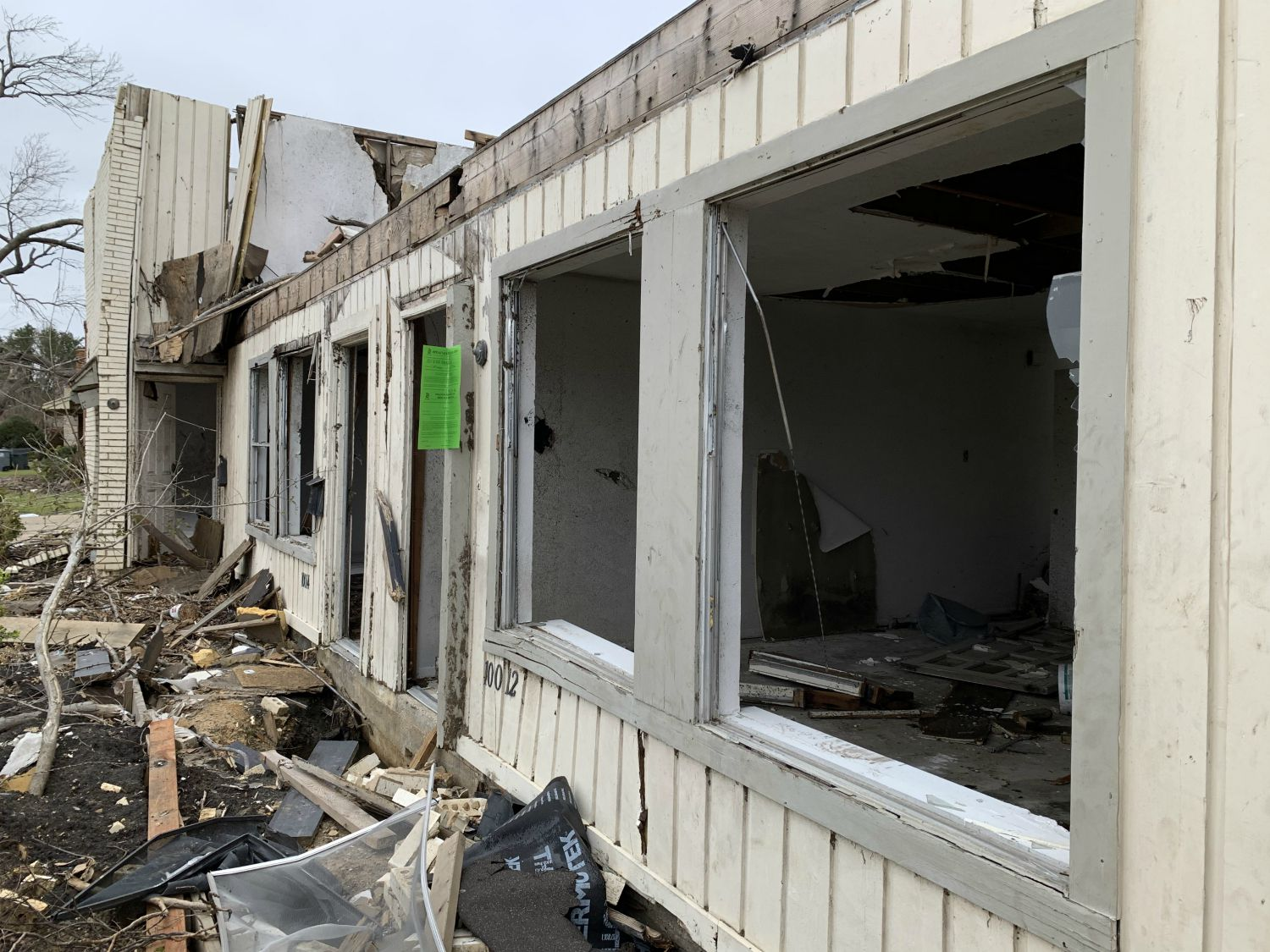 """Code is finally tacking green """"open and vacant"""" violation notices to the front of tornado-damaged homes, like this one on Glenrio Lane near Marsh and Walnut Hill lanes in northwest Dallas."""