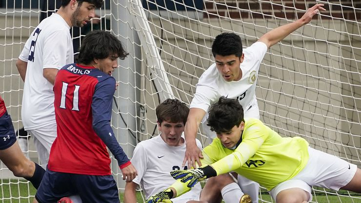 Jesuit goalkeeper Cole Hines (55) makes a save in front of McKinney Boyd forward Jonathan Marquez (11) as Jesuit defenders Benton Bacile (21), Reid Weinberger (24) and Alec Gomez (15) close in during a Class 6A Region I quarterfinal boys high school soccer game on Friday, April 2, 2021, in McKinney.