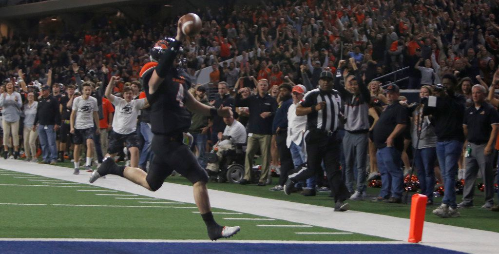 Aledo quarterback Jake Bishop (4) raises the ball over his head and ignites Bearcats fans as he scored the game winning touchdown on a 17-yard scamper to defeat Ennis, 43-36 in overtime to advance. The two teams played their Class 5A Division ll Regional final playoff football game at Frisco Center at The Star in Frisco on December 6, 2019. (Steve Hamm/ Special Contributor)