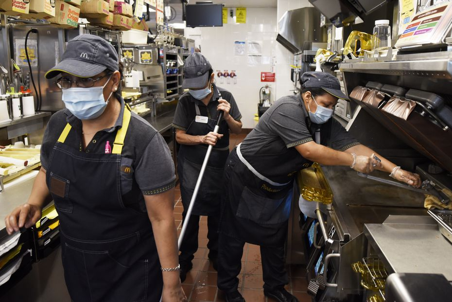 McDonald's employees Maria Soto (left) Lucila Padilla and Emma Gomez, work in the kitchen side of the McDonald's that reopened this week in the Preston Oaks shopping center.