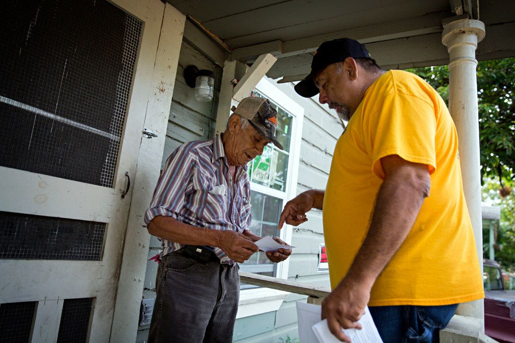 Ronnie Mestas (right), a community leader in West Dallas 1, hands a flier to Fernando Gonzalez outside his rental home on McBroom Street. About 200 tenants are targeted for possible eviction by landlord HMK Ltd. (G.J. McCarthy/Staff Photographer)