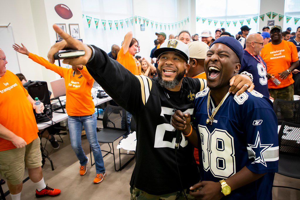"""Adrian Matute (left) and Chris Pouncy laugh together at the end of the monthly """"all-tribe"""" kick off meeting."""