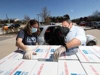 Ricardo Bramila, director de Family Hope Center en Bachman Lake y Robim Bruster ayudaron, el martes, en la distribución de cajas de agua donadas por la Oficina de Manejo de Emergencias de Dallas para residentes en Bachman Lake, un sector mayoría hispana y que viven en apartamentos.