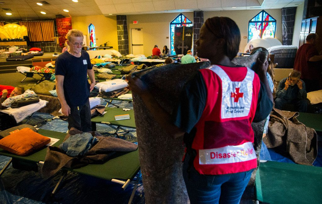 Red Cross volunteer Kainoa Flemons folds a blanket for evacuees at Woodcrest Church after their homes were damaged from rising floodwaters in Lumberton. (Ashley Landis/Staff Photographer)