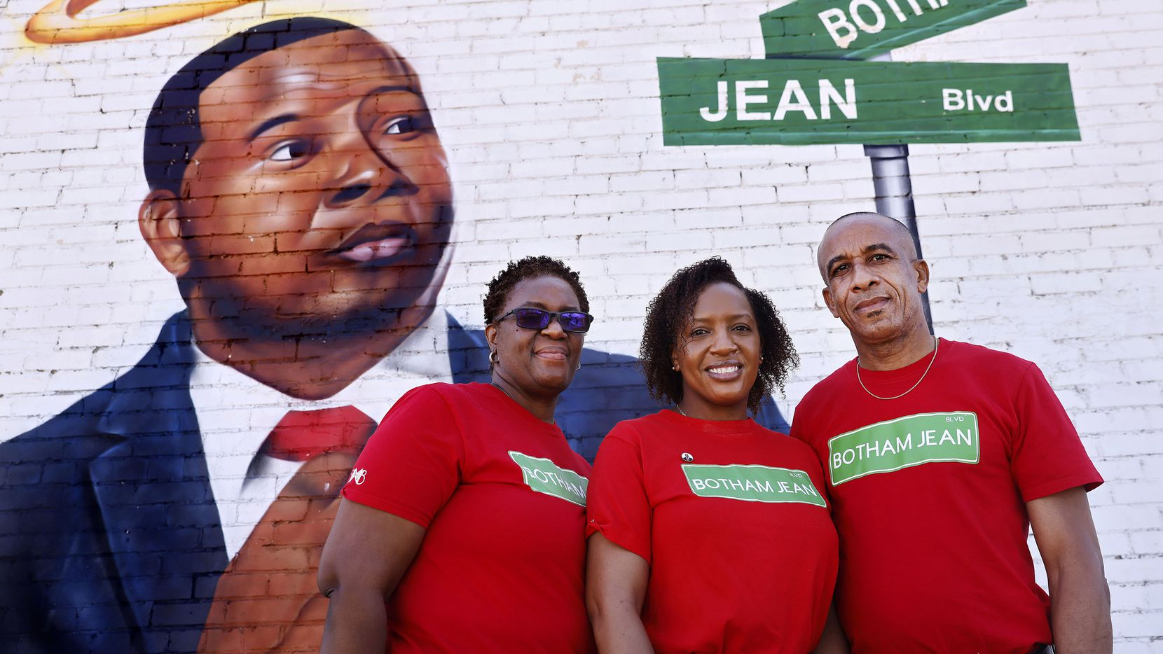 Allison Jean, her daughter, Alissa Findley, and husband, Bertram Jean, pose before a mural of their slain son and brother, Botham Jean, at Lamar and Cadiz streets on Friday, March 27, 2021.