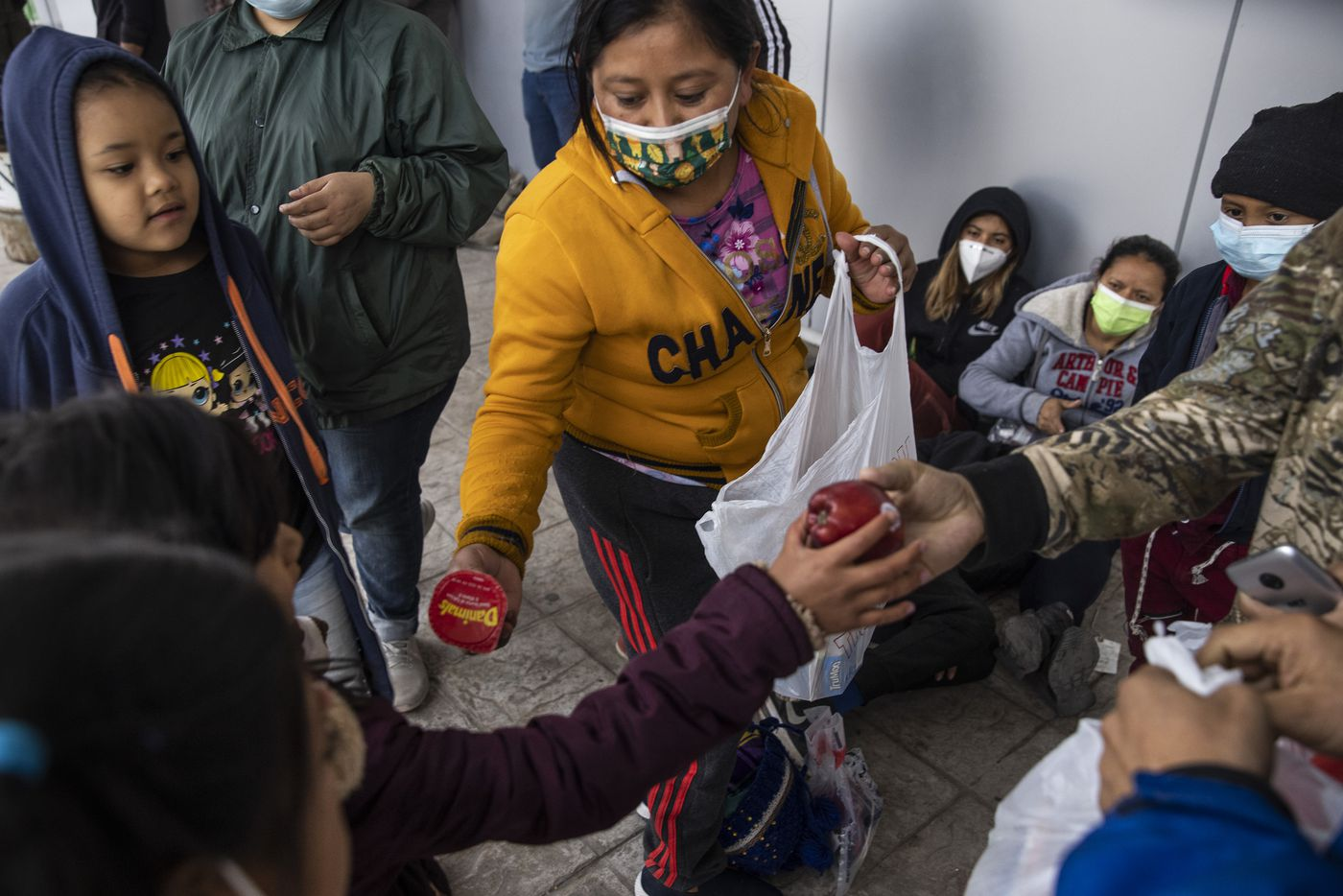 """Isabela Julaj, center, hands out a donated bag food items given to her to share with other migrant families stranded in the plaza near the international bridge leading into Reynosa, in Mexico. Julaj and her two daughters, ages seven and eight, were expelled from the United States overnight under Title 42 — a pandemic-related public order still in place and left over from the Trump administration. The single mother of two said she feels she has no choice but to return to Guatemala. """"There's nothing left for me to do,"""" she said. """"I have very little money left."""""""