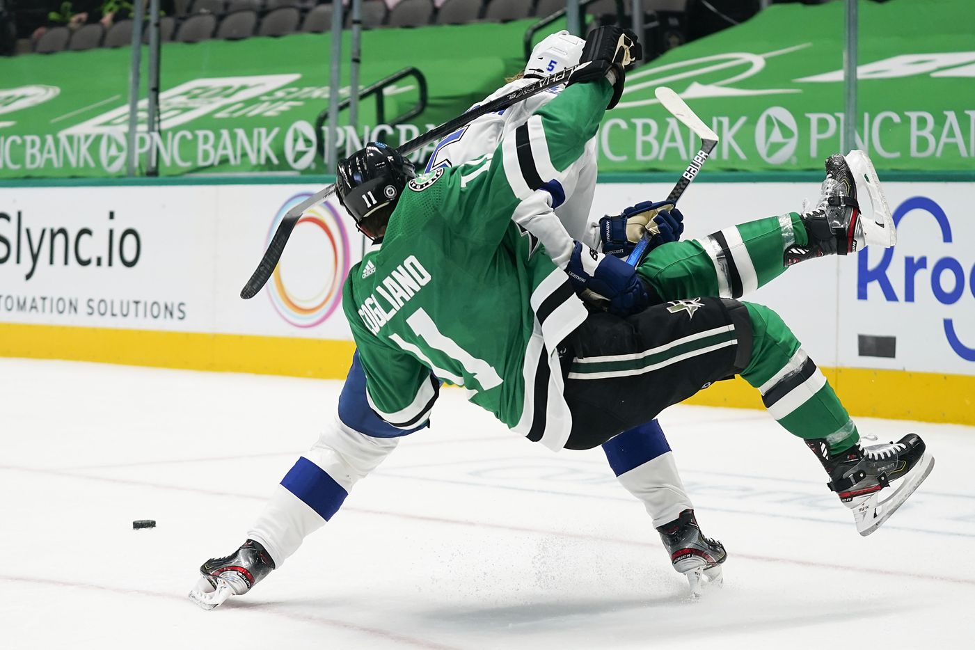 Dallas Stars center Andrew Cogliano (11) is knocked off his skates by Tampa Bay Lightning defenseman Andreas Borgman (5) during the first period of an NHL hockey game at the American Airlines Center on Thursday, March 25, 2021, in Dallas. (Smiley N. Pool/The Dallas Morning News)
