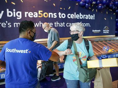 Heartland, Texas resident Jennifer Edmonds thanks a Southwest Airlines employee after receiving a gift box at Dallas Love Field airport on Friday, June 18, 2021, in Dallas. Southwest Airlines celebrated its 50th anniversary with giveaways for passengers at baggage claim as well as trivia games at gates. (Elias Valverde II)