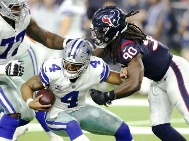 FILE - Cowboys quarterback Dak Prescott (4) fends off Texans linebacker Jadeveon Clowney (90) during the second half of a game at NRG Stadium in Houston on Sunday, Oct. 7, 2018.