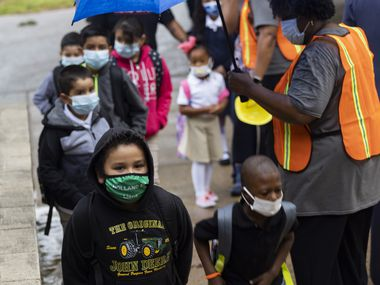 A federal judge will hear arguments over Gov. Greg Abbott's mask mandate ban in schools. Students wore masks as they headed into the first day of school on Aug. 2 at H.I. Holland Elementary School in Dallas.