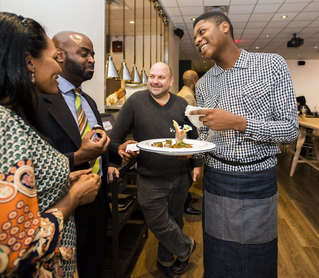 Intern Malik Runnels (right) of Pleasant Grove serves hors d'oeuvres at Cafe Momentum's grand opening in 2015.  The first-of-its-kind restaurant in Dallas employs juvenile offenders and teaches them skills like cooking, dish washing and serving.