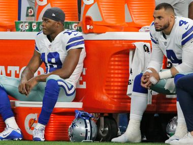FILE - Cowboys wide receiver Amari Cooper (19) and quarterback Dak Prescott (4) on the sideline as time winds down on a 23-0 loss to the Colts at Lucas Oil Stadium in Indianapolis on Sunday, Dec. 16, 2018.