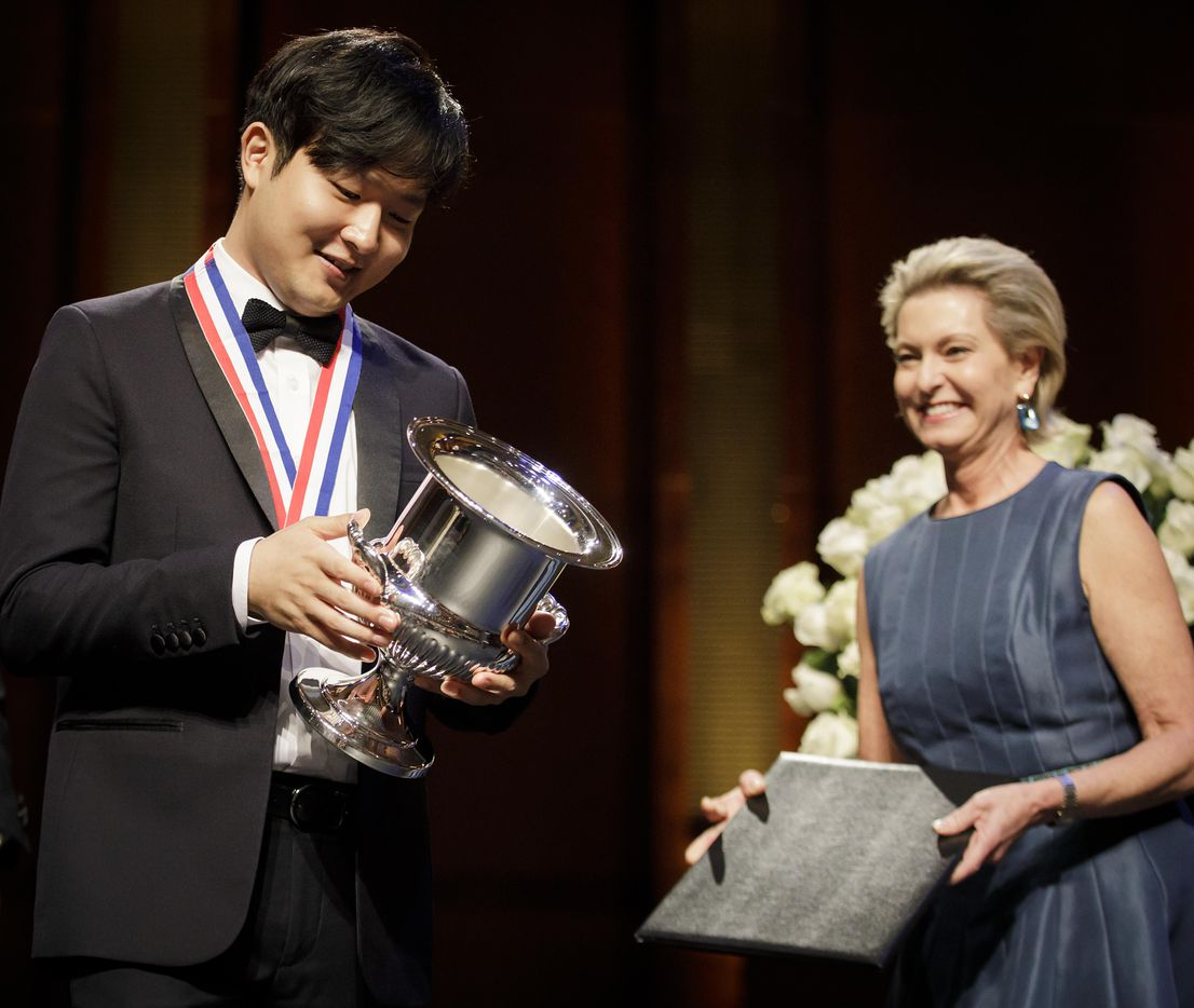 Gold medalist Yekwon Sunwoo of South Korea holds the Van Cliburn Winner's Cup as Cliburn Chairman of the Board (right) Carla Kemp Thompson looks on during the Van Cliburn International Piano Competition awards ceremony at the Bass Performance Hall in Fort Worth on Saturday, June 10, 2017. (Smiley N. Pool/The Dallas Morning News)