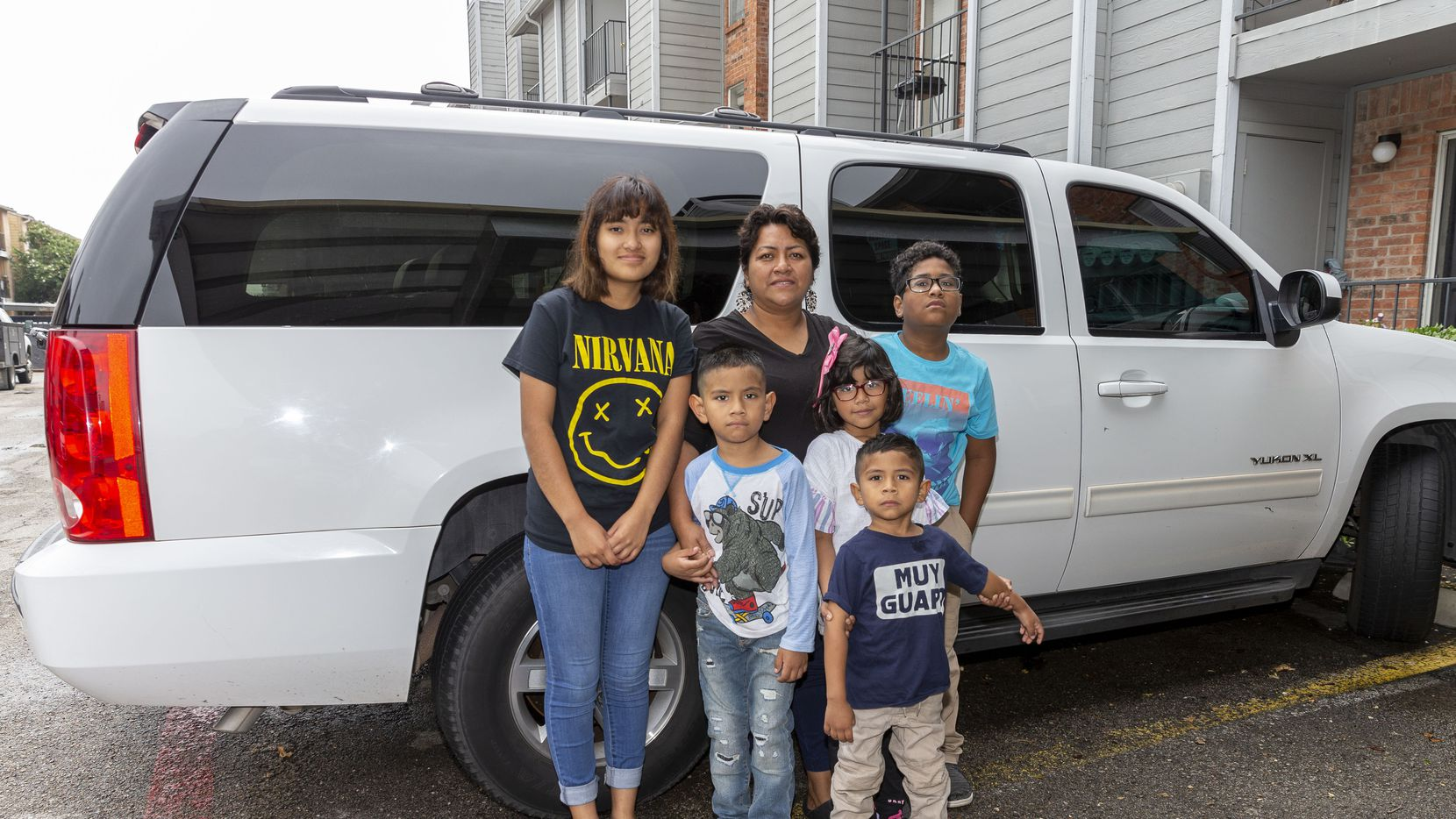 Lily de la Cruz with five of her children and the vehicle they lived in for part of 2020.