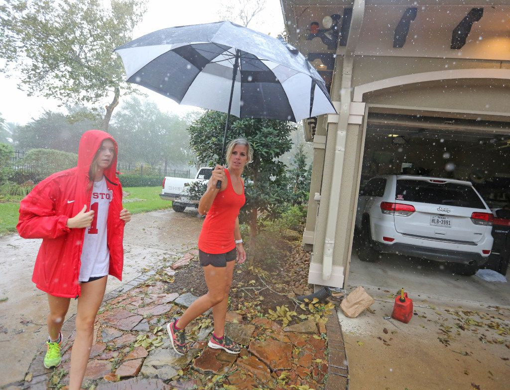 Abby Odneal, left, and her mother Ashley dodge raindrops to view the damage on the family residence after a tornado spawned by Hurricane Harvey hit the Sienna Plantation subdivision southeast of Houston on Saturday, August 26, 2017. (Louis DeLuca/The Dallas Morning News)