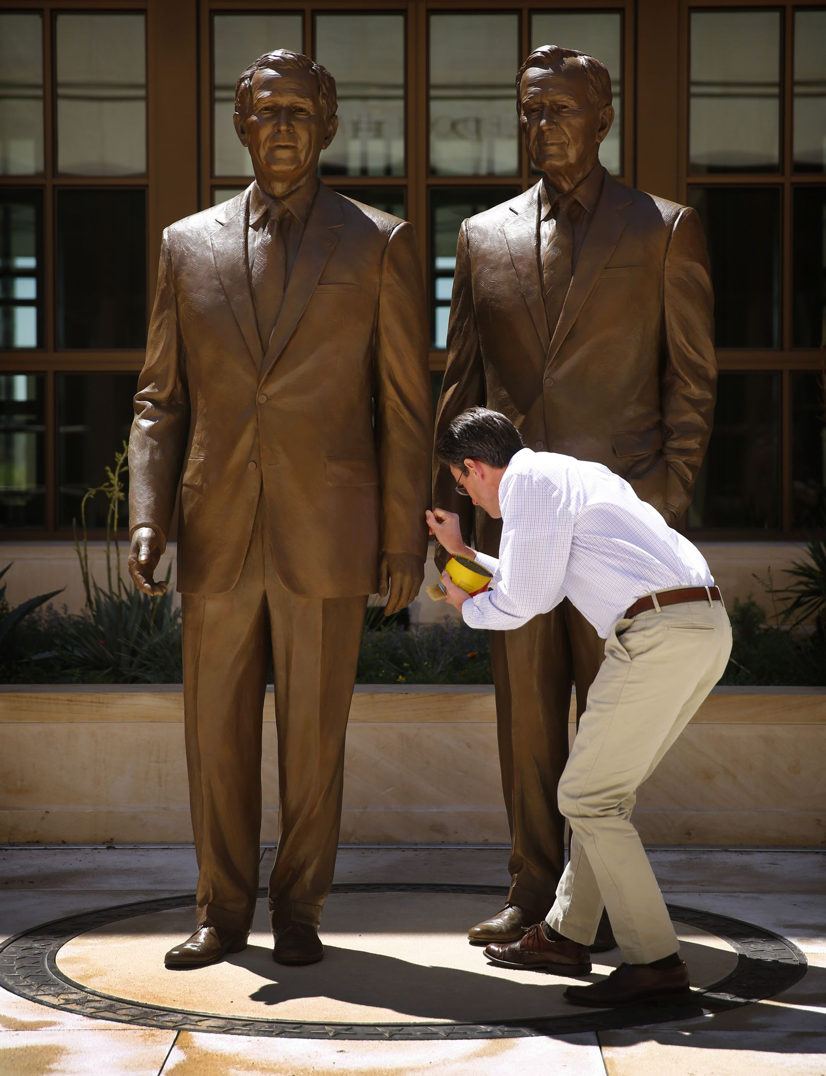 2013: Sculptor Chas Fagan of Charlotte applies wax to the 8-foot bronze statues he created of former Presidents George W. Bush (left) and George H.W. Bush in the courtyard of the George W. Bush Presidential Center in University Park.