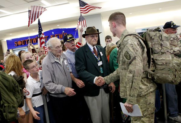 """Family, friends, and volunteers (no names available) greet troops on March 14, 2012, on the last official day of the """"Welcome Home a Hero"""" program to greet military R-and-R flights passing through Dallas-Fort Worth International Airport."""