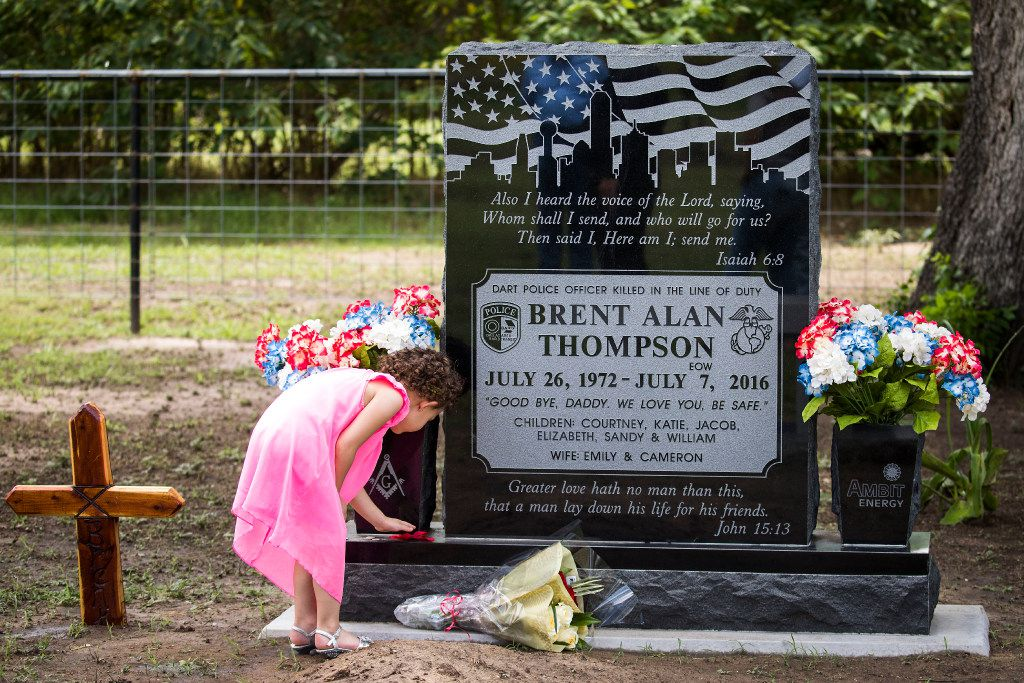 Kristen Raley, 5, placed a flower on the grave of Officer Brent Thompson in June as extended family visited after a nearby reunion. Police officers visit the grave and leave flowers, coins and full bottles of Shiner Bock.