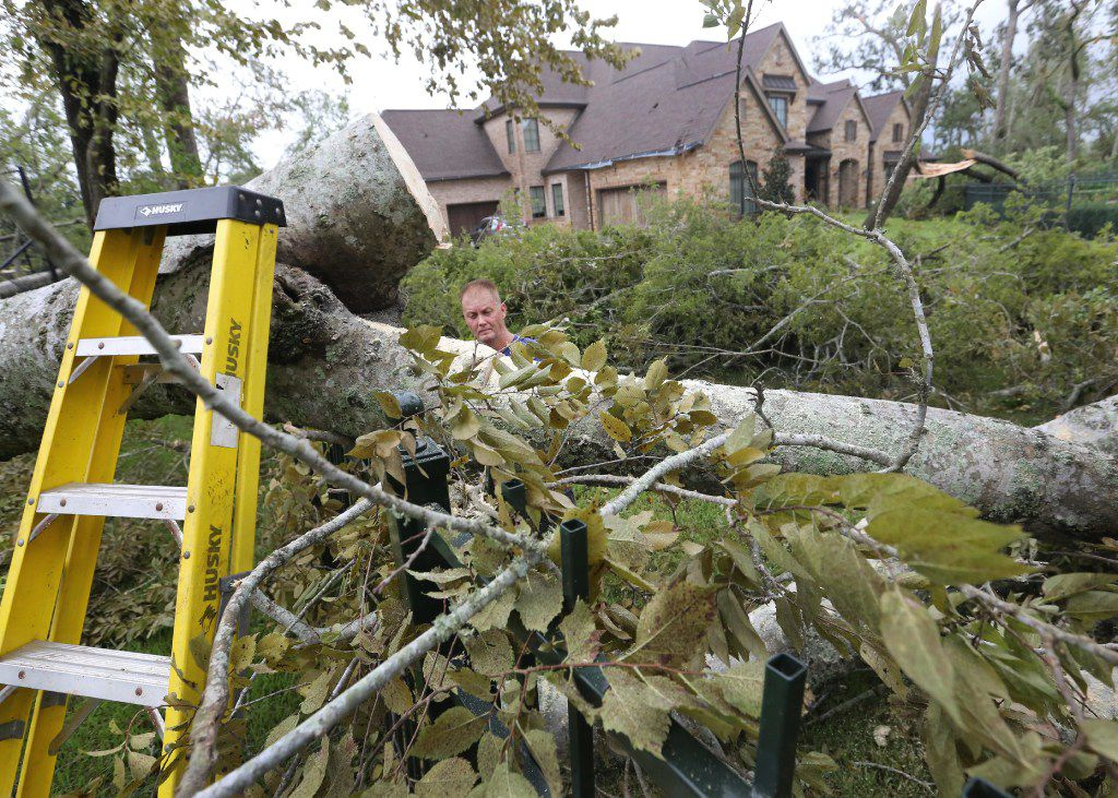 Crews work to chop up trees that fell on the Odneal family home in Sienna Plantation.