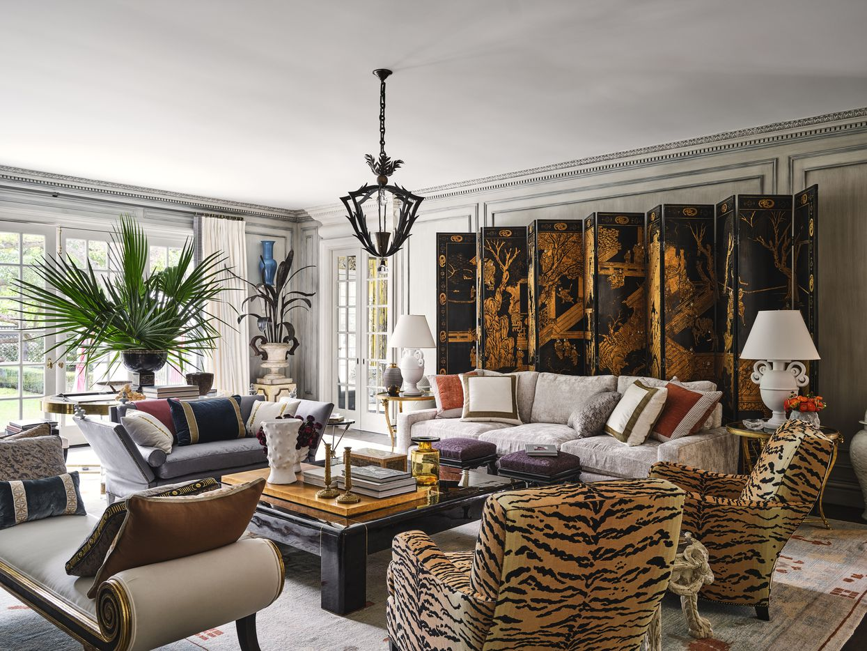 The living room in the 2021 Kips Bay Decorator Show House Dallas was designed by Michael Aiduss Interiors and Architecture. The room was designed with Parisian influences in mind and has elaborate plaster moldings, a mix of patterns and color and a striking Chinese black lacquer panel screen tucked behind the couch.