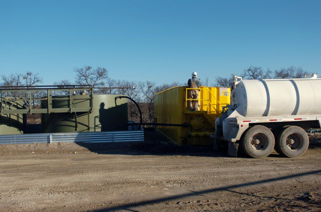 A tanker truck driver checks on a tank at an Aruba Petroleum gas well in Wise County in 2010. (Denton Record-Chronicle)