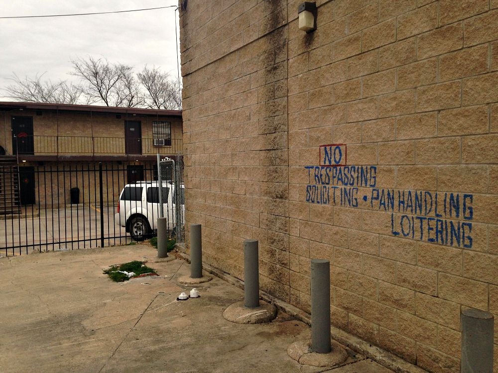 The signage on the liquor store that backs up to the complex at 3006 Holmes Street in South Dallas