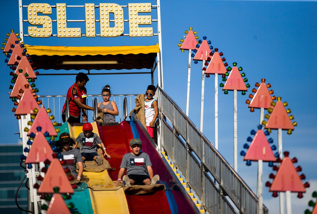 Children slide down a giant slide during Kaboom Town festivities in Addison, Texas on Tuesday, July 3, 2018. (Ashley Landis/The Dallas Morning News)