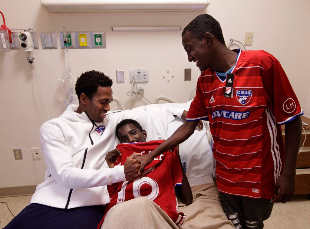 FC Dallas player Atiba Harris (left) visits with 16-year-old Tamirat Bogale and Tamirat's brother Markos Bogale at Medical Center of Plano.