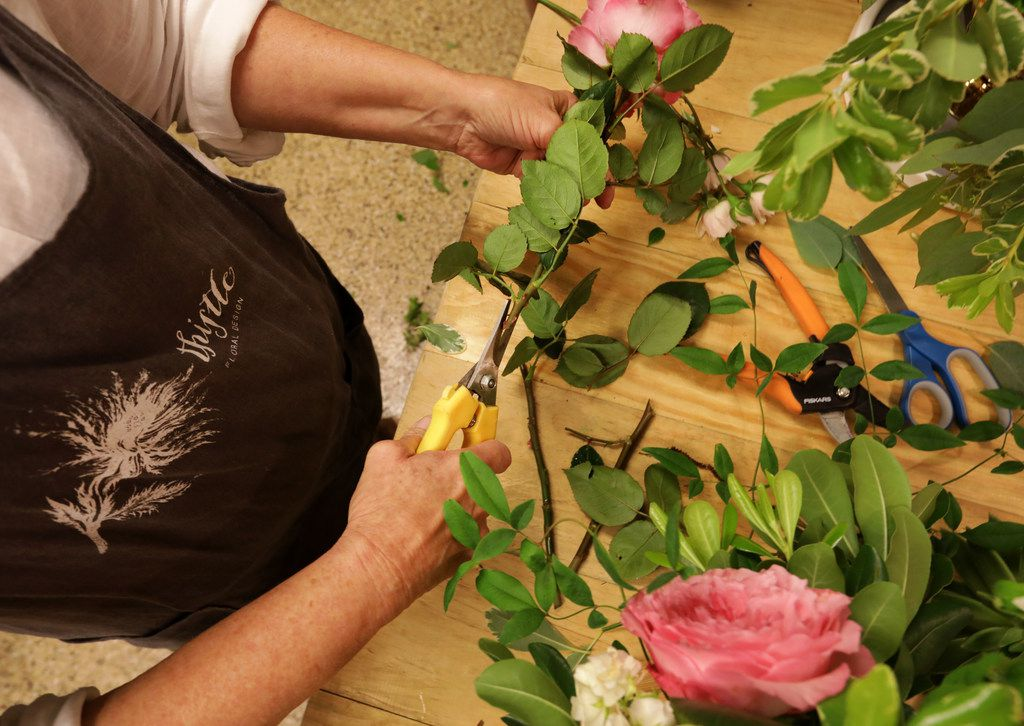 Thistle Floral Design owner Jan Barstad trims the stems of flowers.