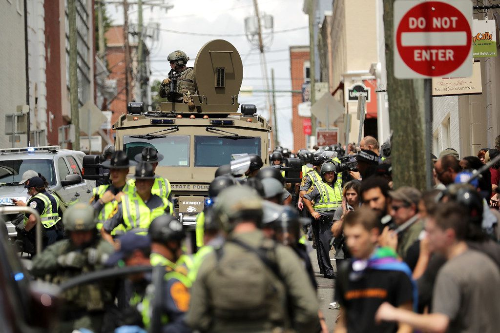 "CHARLOTTESVILLE, VA - AUGUST 12:  A Virginia State Police officer in riot gear keeps watch from the top of an armored vehicle after car plowed through a crowd of counter-demonstrators marching through the downtown shopping district August 12, 2017 in Charlottesville, Virginia. The care plowed through the crowed following the shutdown of the Unite the Right rally by police after white nationalists, neo-Nazis and members of the ""alt-right"" and counter-protesters clashed near Lee Park, where a statue of Confederate General Robert E. Lee is slated to be removed.  (Photo by Chip Somodevilla/Getty Images)"