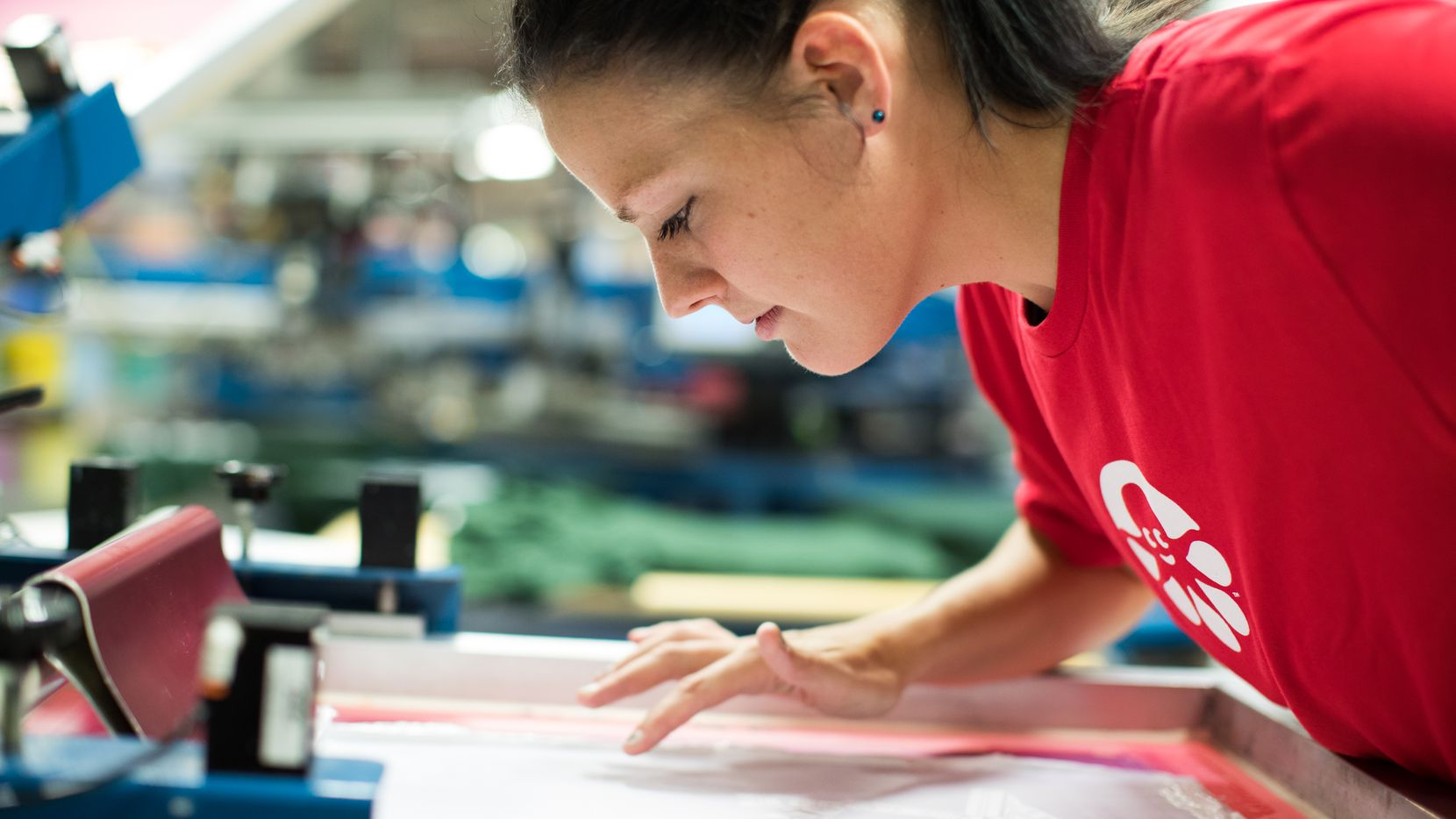 A Custom Ink worker checks on a design on the production floor. The company makes custom T-shirts and other apparel.