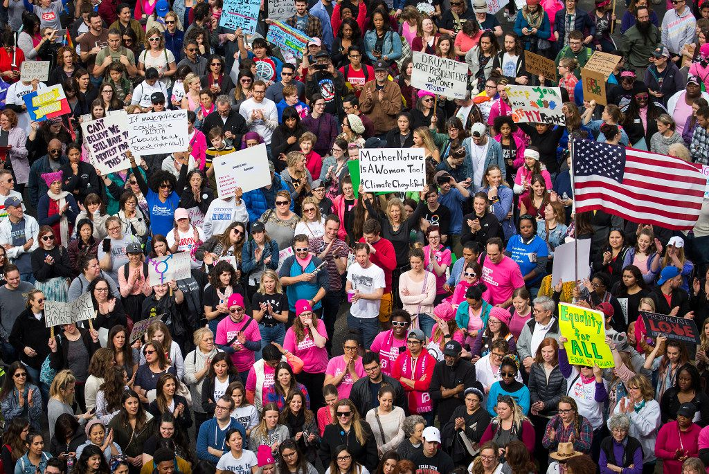 Participants in the Women's March cheer speakers at a rally outside the Communications Workers of America Hall in Dallas.