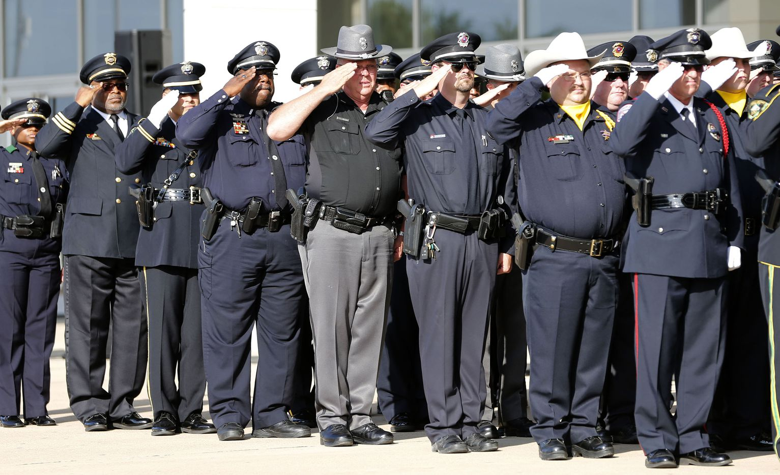 Officers from various locations salute as DART Officer Brent Thompson is carried inside for a memorial service at The Potter's House in Dallas on Wednesday, July 13, 2016. Thompson was one of five officers killed last week when a gunman opened fire during a Black Lives Matter rally in downtown Dallas.