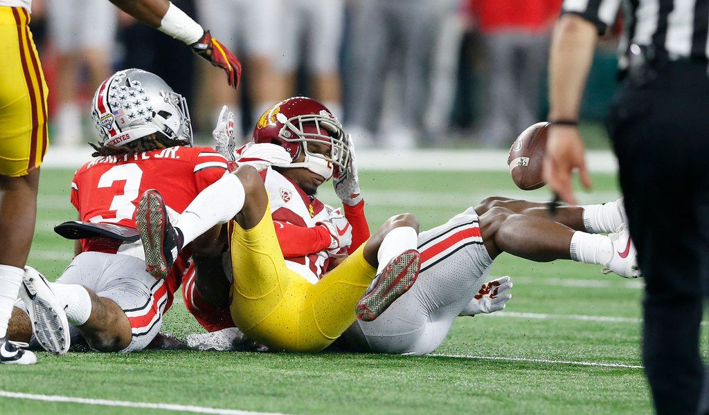 USC Trojans wide receiver Deontay Burnett (80) fumbles the ball as he is defended by Ohio State Buckeyes cornerback Damon Arnette (3) during the first quarter of play in the Cotton Bowl at AT&T Stadium in Arlington, Texas on Friday, December 29, 2017. (Vernon Bryant/The Dallas Morning News)