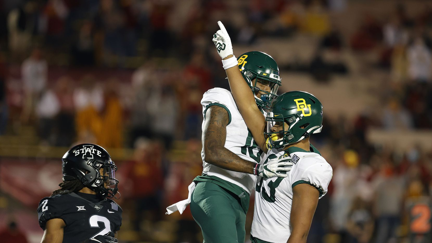 Baylor tight end Drake Dabney, right, reacts after running in a touchdown as Baylor wide receiver Jared Atkinson, center, comes into celebrate as Iowa State defensive back Datrone Young, left, is late to the play during the first half of an NCAA college football game, Saturday, Nov. 7, 2020, in Ames. (AP Photo/Matthew Putney)