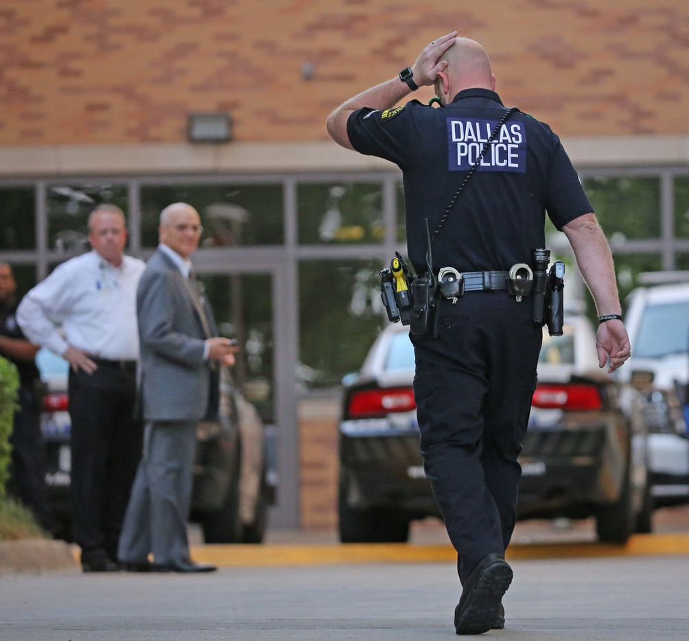 A Dallas Police officer walks to the entrance to the emergency room at Presbyterian Hospital in Dallas. Two Dallas policemen were reportedly shot at a nearby Home Depot and reportedly were transported to the Dallas hospital on Tuesday, April 24, 2018.  (Louis DeLuca/Staff Photographer)
