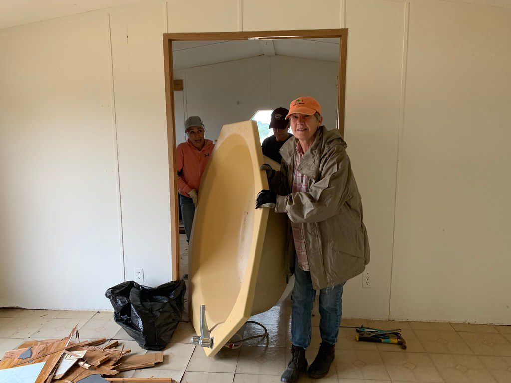 Carolyn Burns (in front) tackles removing a bathtub with friends from her church. Only one of the women is under 70. Carolyn and Scott Burns are renovating two mobile homes, including this 1990 Redman singlewide.