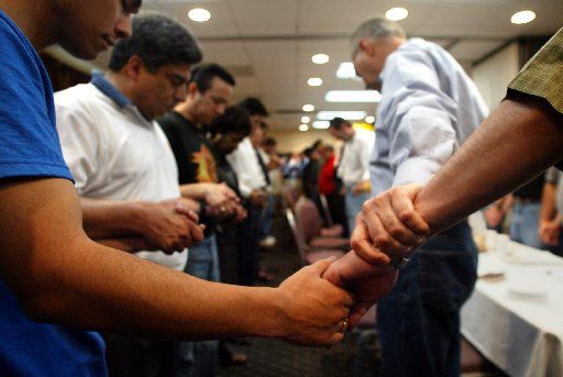 Texas state Democratic representatives held hands in prayer to open their morning session in a conference room at the Holiday Inn in Ardmore, Okla., on May 14, 2003.  The Texas Democrats left the state in protest over proposed redistricting by Republican leadership in the Texas House.