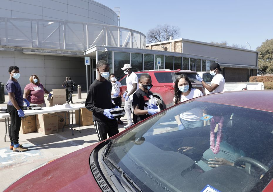 A team of people at Mattie Nash Myrtle Davis Recreation Center hand out hot food from Off the Bone Barbeque on Tuesday, Feb. 23, 2021. World Central Kitchen has partnered with Dallas restaurants in an effort to help citizens affected by last week's snowstorm.