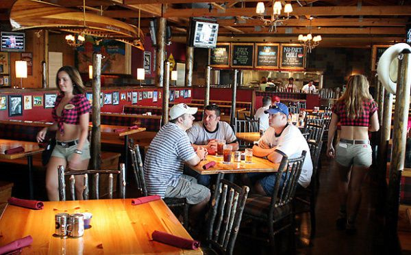 Twin Peaks co-founder Randy DeWitt sees the chain as an upscale version of Hooters, with waitresses in midriff-baring red-plaid lumberjack shirts and short shorts serving mostly male guests in large, lodge-themed dining rooms replete with HDTV screens.