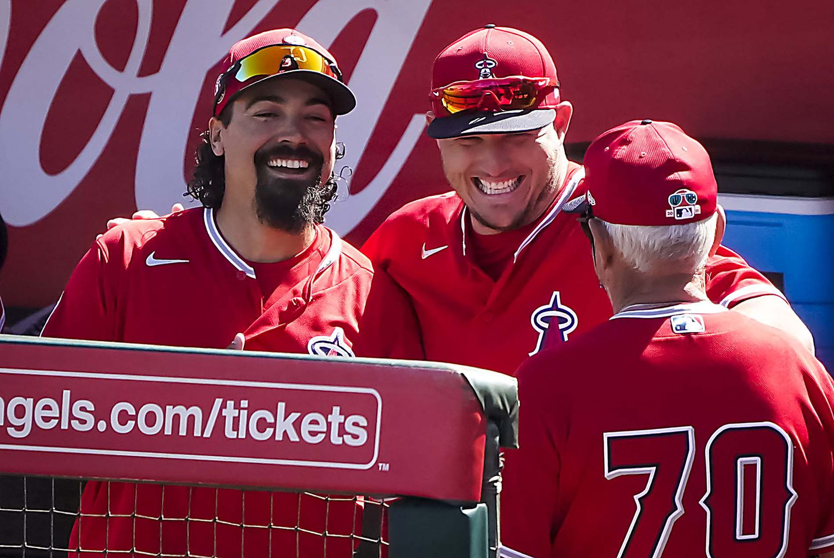 Los Angeles Angels third baseman Anthony Rendon (left) and center fielder Mike Trout laugh with manager Joe Maddon (70) in the dugout before a spring training game against the Texas Rangers at Tempe Diablo Stadium on Wednesday, March 3, 2021, in Tempe, Ariz. (Smiley N. Pool/The Dallas Morning News)
