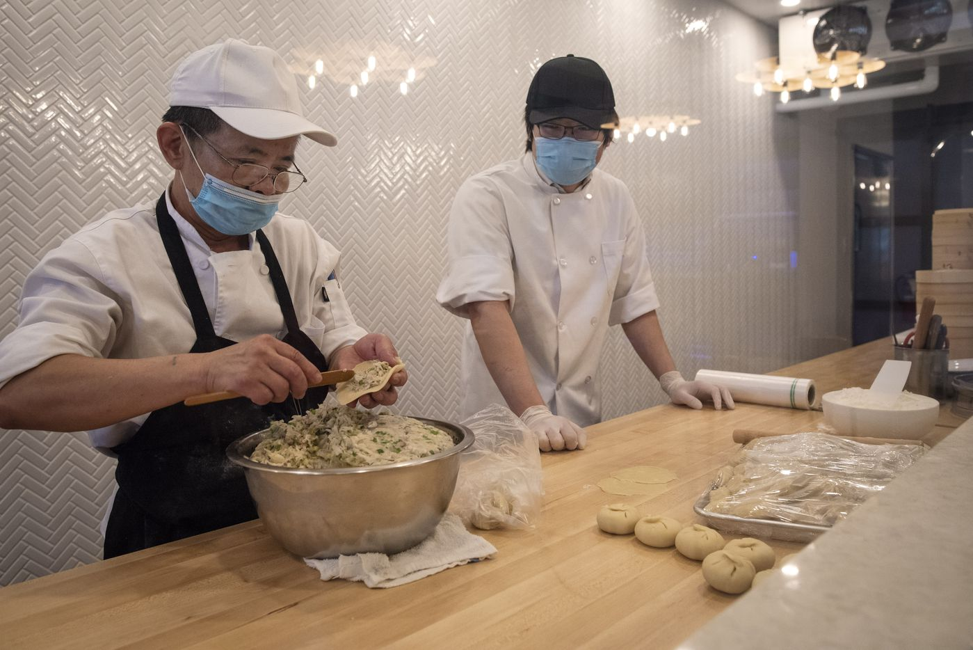 Dumpling chef Harrison Huang, left, and owner Ian Peng behind the dumpling window at Kitchen Master restaurant in Frisco, Sunday, May 31, 2020.